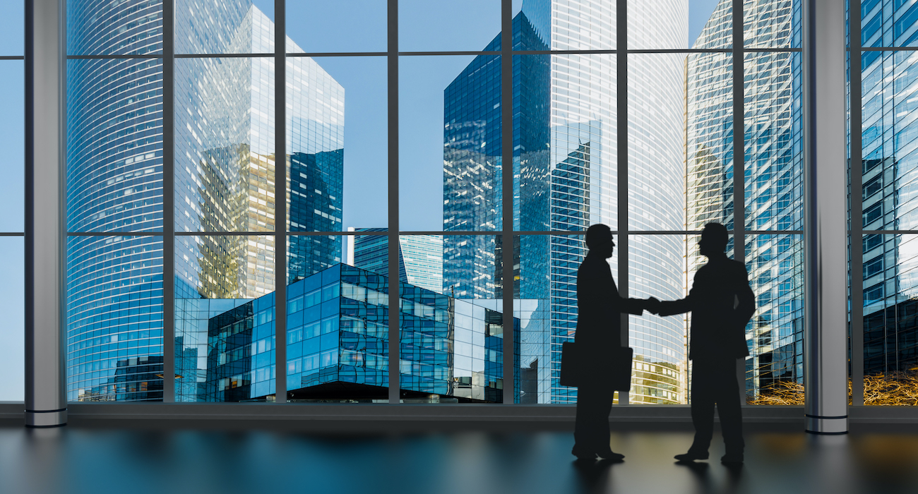 businessman shaking hands inside a business tower