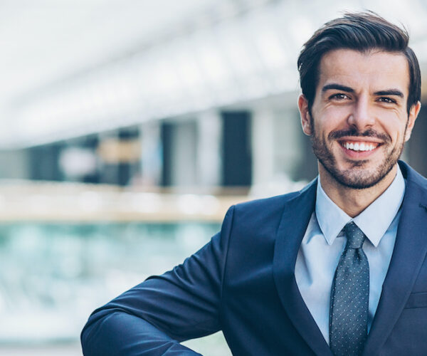 Smiling lawyer standing inside modern office office building, with copy space.
