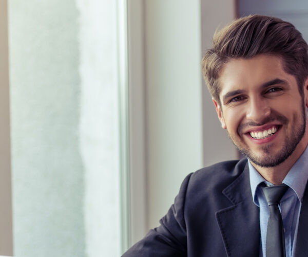 Portrait of handsome lawyer in formal suit using a laptop, looking at camera and smiling while working in office